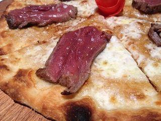 Pizza pepito de ternera, con una rodaja de solomillo. Se come doblando la pizza como si fuera un taco mexicano