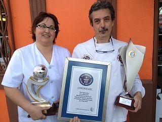 A la puerta del restaurante Marquinetti. Jesús y su mujer Emi muestran algunos de los trofeos logrados en los últimos 8 años