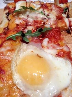 Pizza con huevos fritos y panceta de cerdo ibérico. Alegoría del plato tradicional español en versión pizza