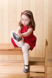 Niña poniéndose los zapatos sin ayuda