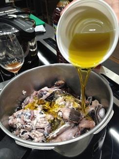 Añadiendo aceite de oliva virgen extra a los despojps de merluza