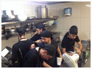 Seis cocineros acelerados en dos metros cuadrados.