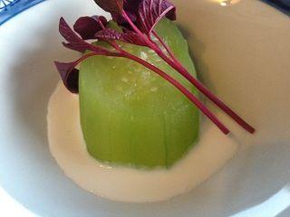 Tronco de pepino marinado sobre una crema de queso de cabra y hojas de amaranto