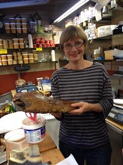 Hanna Andström propietaria del comercio de Helsinki mostrando una pieza de halibut ahumado en caliente, excelente