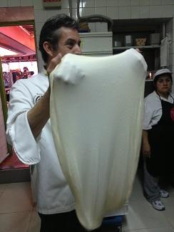 Jesús Marquina con una masa de pizza de larga fermentación estirada  mano y casi transparente