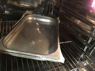 En el horno dos bandejas. La inferior contiene las patatas, la superior una capa de agua que actúa de peso