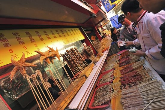China, Beijing, large group of skewered meat and lobsters for sale while vendor taking money from customer at market stall
