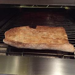 Tostada de pan de cristal en la boca de la tostadora para el templado final