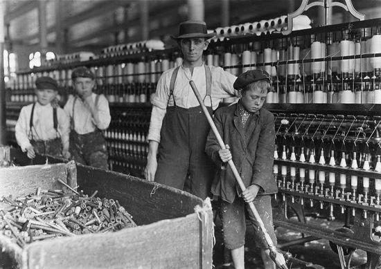 Niño barriendo en fábrica textil