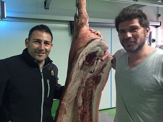 Javier Murias, carnicero, y David Reartes con un canal de porc negre ibicenco