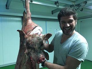 David Reartes junto a una pieza de porc negre con su propia cabeza