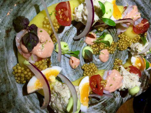 Causa limeña ilustrada  con crema de ají marillo, cangrejo, aguacate, huevos y mahoesa