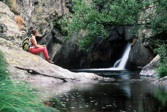 Una excursionista, sentada en una roca ante la Poza Negra del río Cambrones Andrés Campos