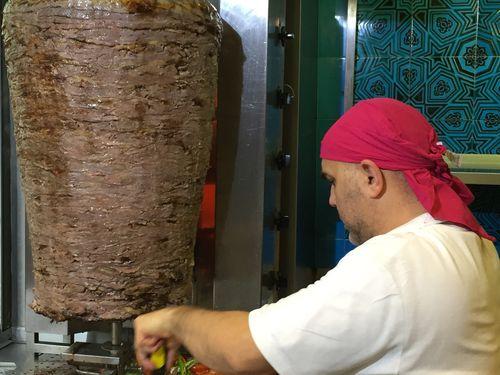 Preparando los döner kebab con el gran rollo de carne de cordero prensada en el restaurante Hasir