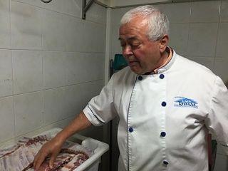 Tomás Galván mostrando arcones refigerados con costillas de cerdo saladas