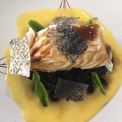Pescado sobre cuscus negro sobre crema de huevo. Rociado con un caldo de pescado concentrado con cáscaras de naranja amarga  y cortezas de la piel del pescado
