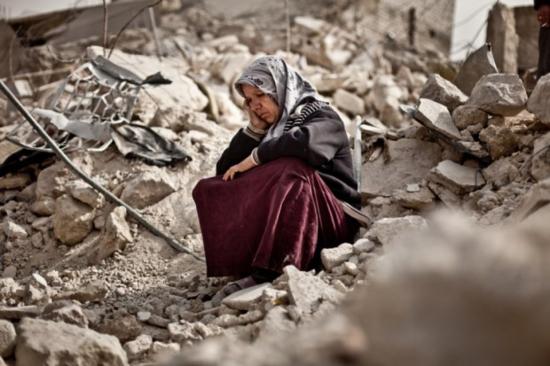 Zakia-Abdullah-una-mujer-siria-sobre-los-escombros-de-su-vivienda-tras-la-explosión-de-un-misil-en-Alepo-Imagen-de-Pablo-Tosco-620x413