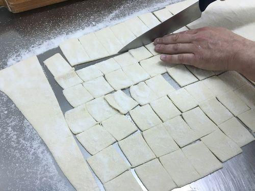 Cuadraditos de milhojas azucarados antes de entrar en el horno